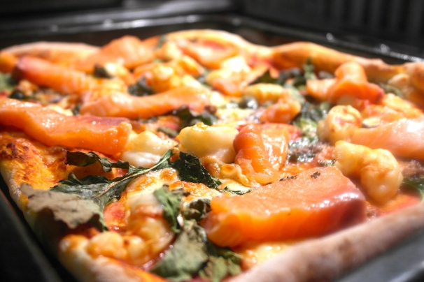 Put the salmon on when the rest is cooked and heat it through in a warm oven… probably the one you used to cook your pizza in