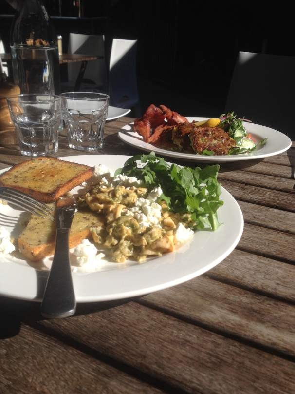 Green scrambled eggs in the foreground ($16 I think), zucchini fritters in the back ground ($16.50) with a side of bacon ($4)