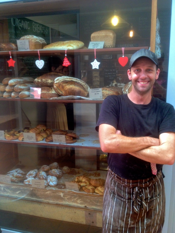 Pastry chef Mark Conroy looking photogenic as hell in front of a window of tasty treats